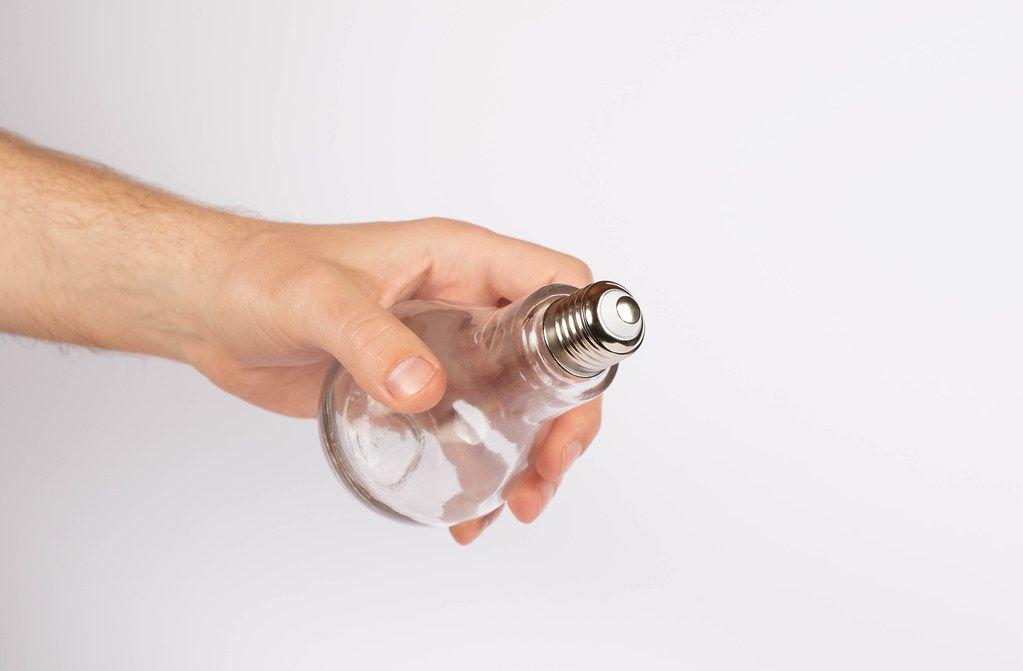 Hand hält eine Glühbirne vor weißem Hintergrund