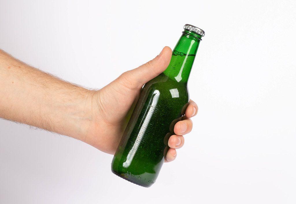 Hand hält eine grüne Bierflasche ohne Etikett, isoliert vor weißem Hintergrund