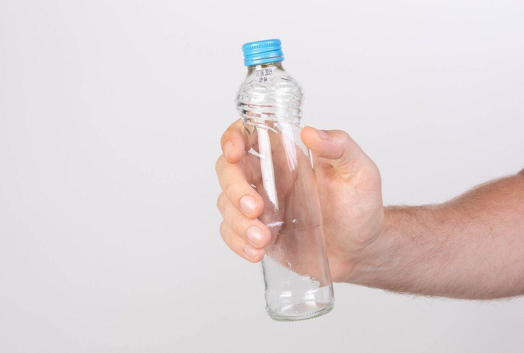 Hand hält eine leere Glasflasche mit Drehverschluss vor weißem Hintergrund
