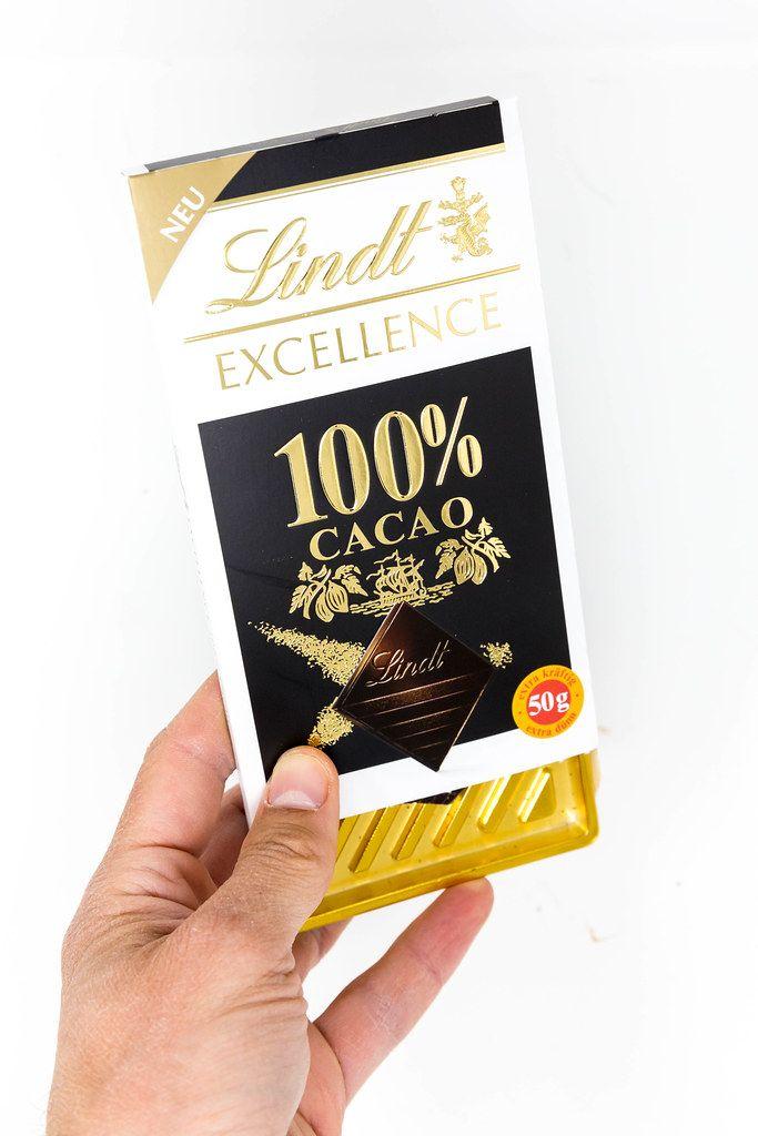 Hand hält eine Lindt Excellence 100 Prozent Kakao Schokoladentafel vor weißem Hintergrund