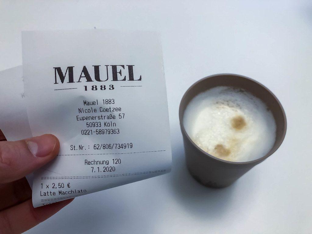Hand hält einen Beleg für den Kauf von einem Latte Macchiato in einem Café in Köln