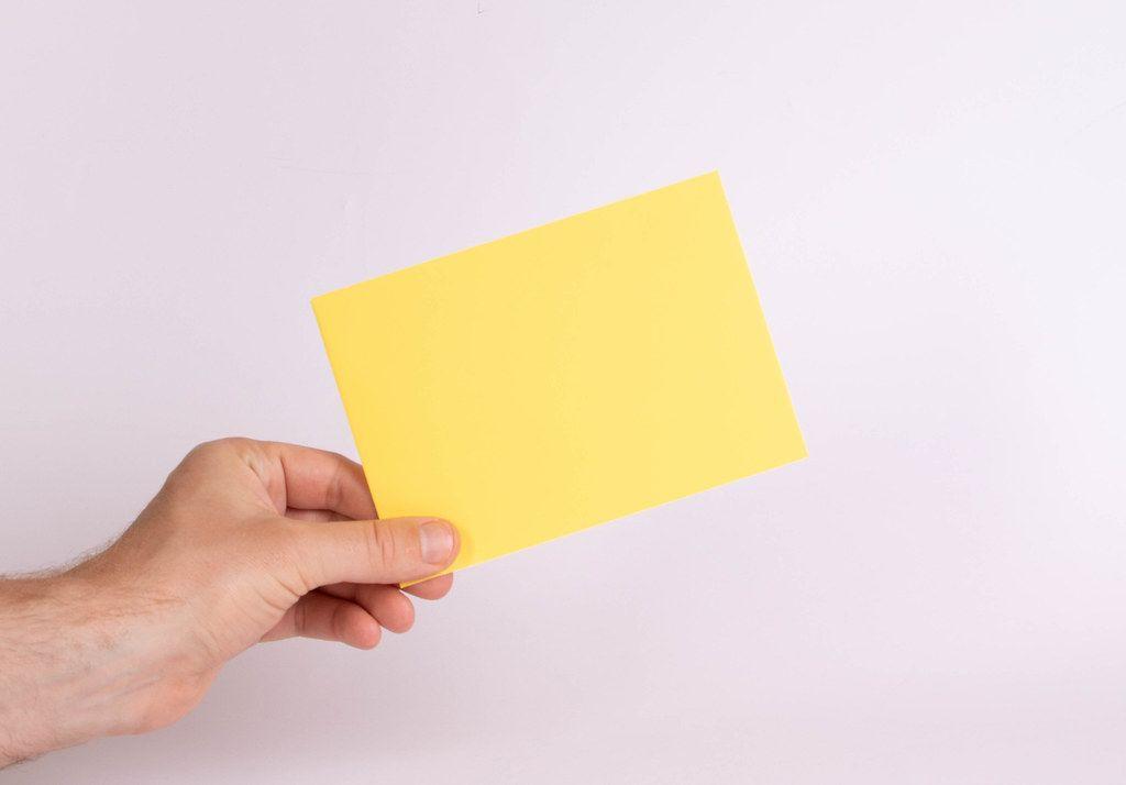 Hand hält einen gelben Umschlag vor weißem Hintergrund