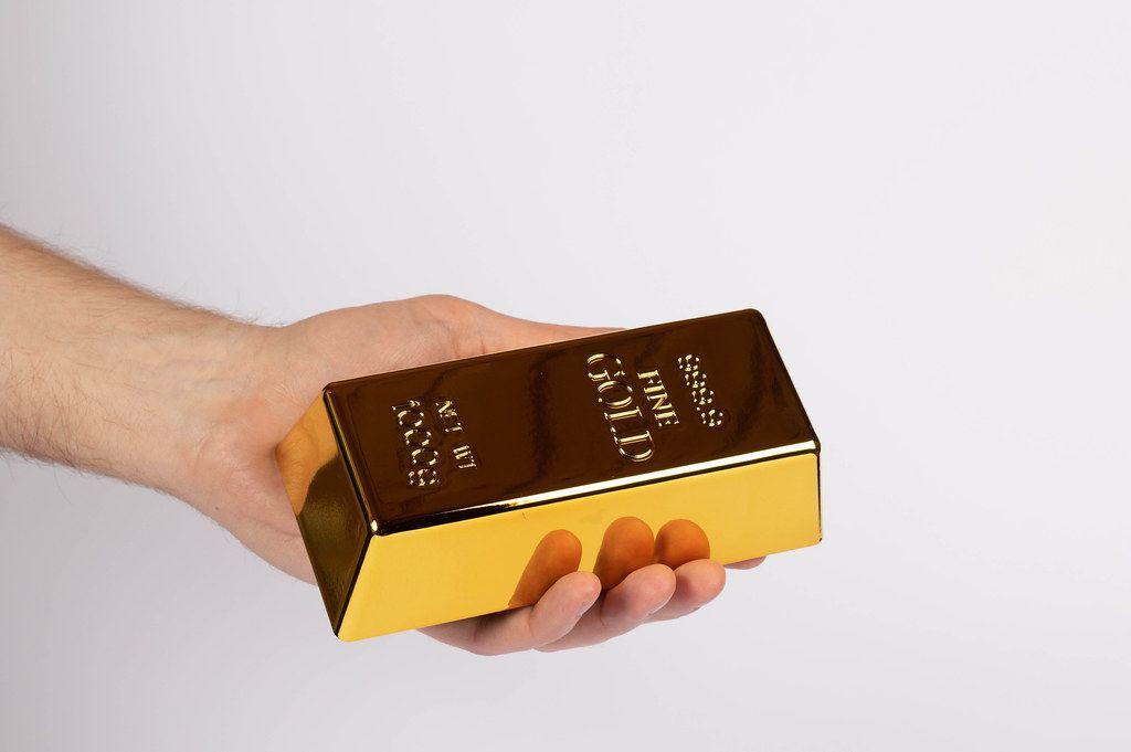 Hand hält einen Goldbarren vor weißem Hintergrund