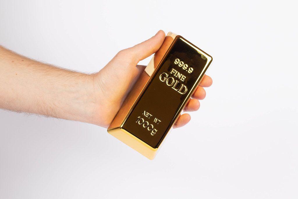 Hand hält einen Goldbarren
