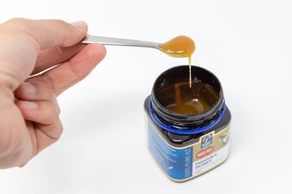 Hand hält einen Löffel mit flüssigem Honig über da Honigglas