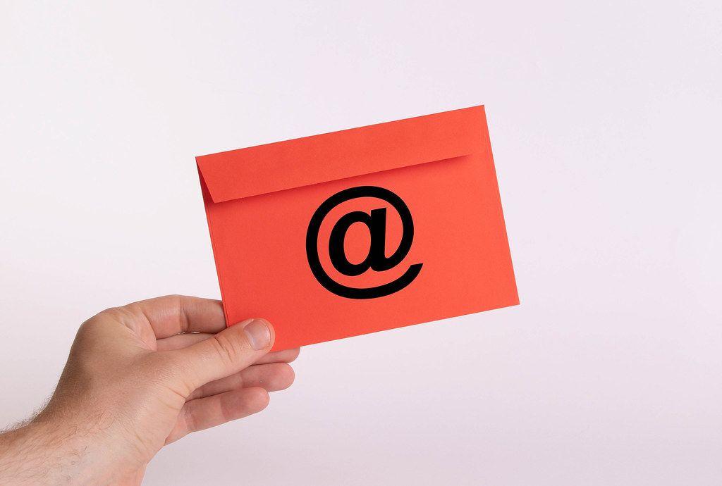 Hand hält einen roten Umschlag vor weißem Hintergrund, mit dem @-Zeichen