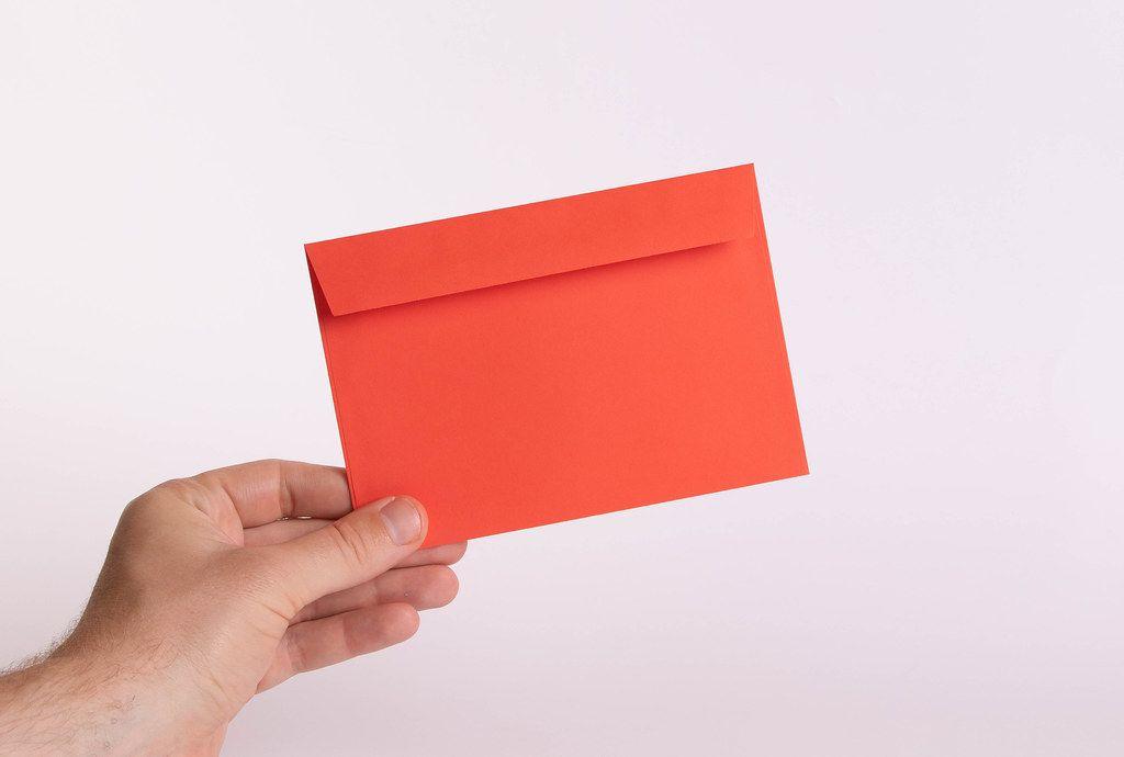 Hand hält einen roten Umschlag vor weißem Hintergrund