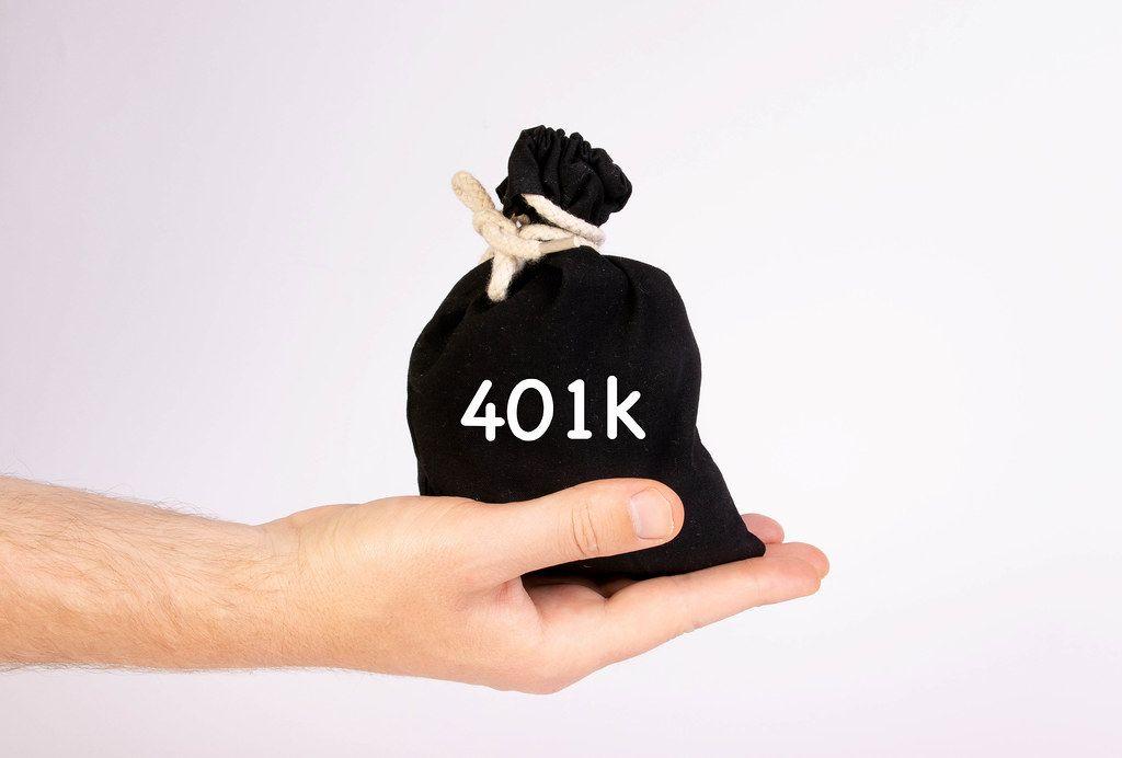 Hand hält einen schwarzen Sack / Geldsäckchen, mit der Aufschrift