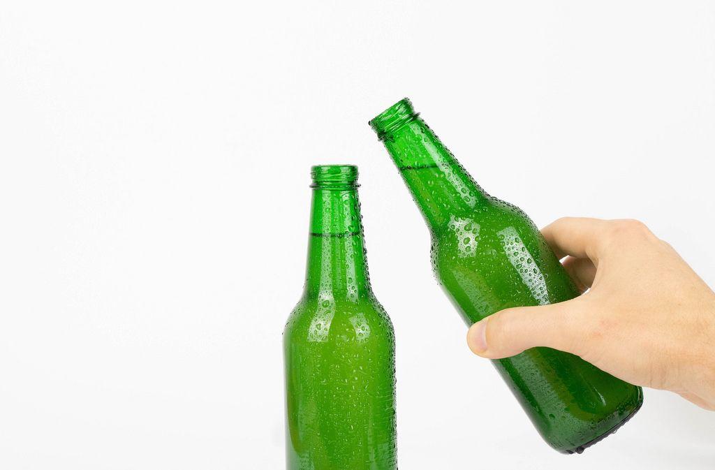 Hand hält Flasche zum Anstoßen bereit