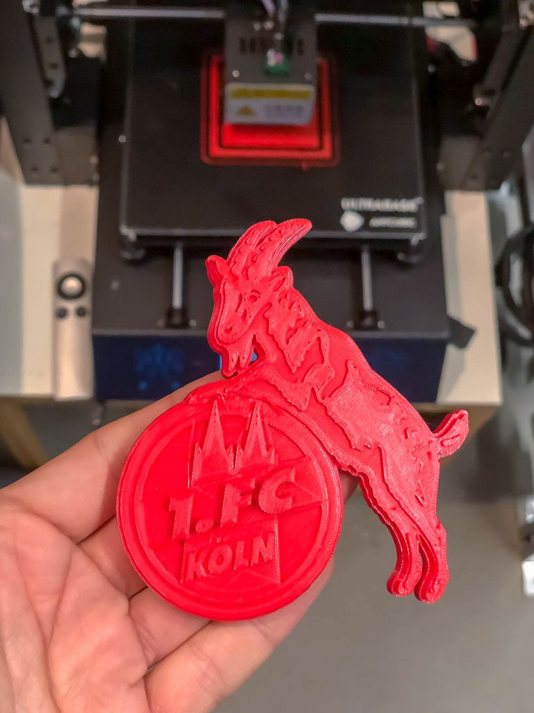 Hand hält Geißbock Hennes, das Maskottchen des 1. FC Köln als roter 3D-Druck vor dem 3D-Drucker