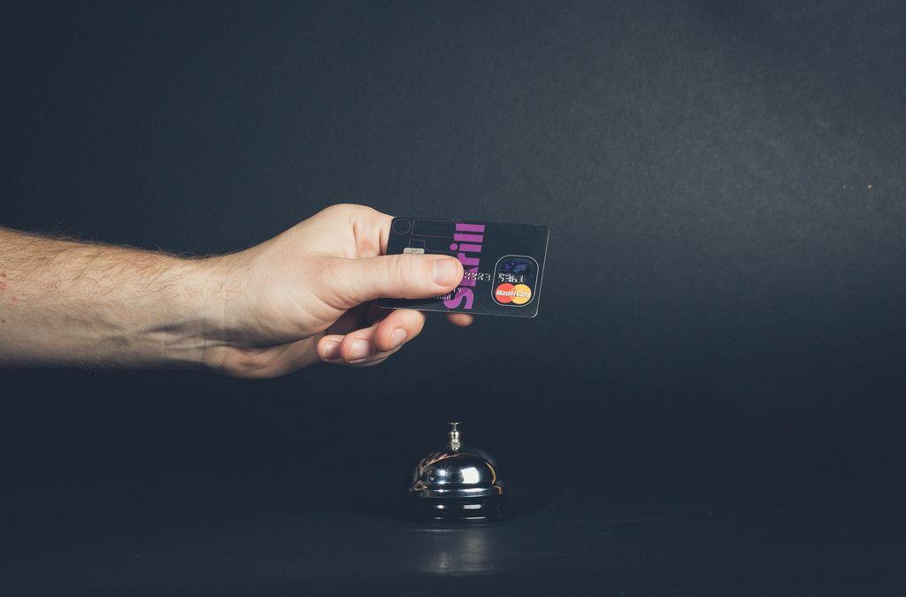 Hand hält Kreditkarte über Hotelglocke symbolisiert Bezahlen von Hotelzimmer mit Kreditkarte