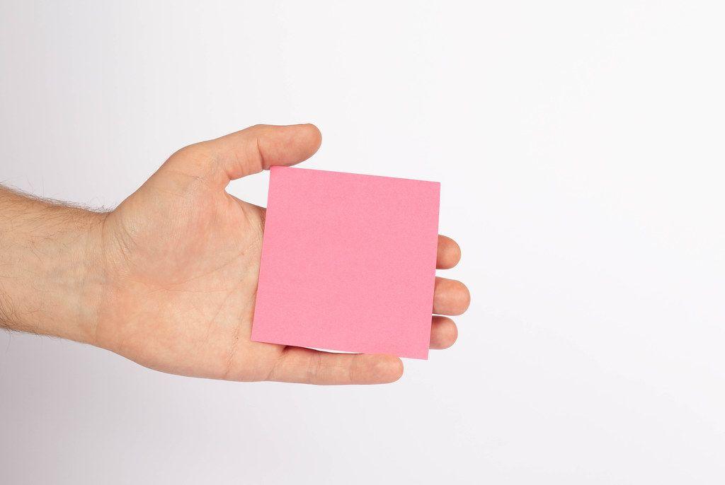 Hand hält leeres, pinkfarbenes Blatt Papier, isoliert vor weißem Hintergrund