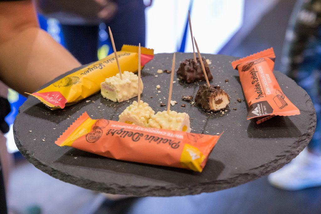 Hand hält Multipower Protein Delight Schokoladenbarren auf einen Probierteller in verschiedenen Geschmäcken: Zartbitterschokolade Moccha, Weiße Schokolade Tropical & Weiße Schokolade Erdbeere