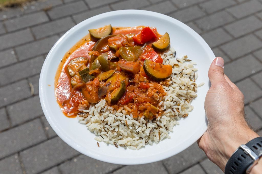 Hand hält veganes Ratatouille mit Wildreis auf weißem Teller auf dem BarCamp in Koblenz