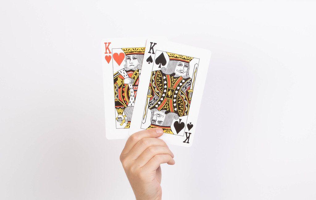 Hand hält zwei Könige-Spielkarten vor weißem Hintergrund