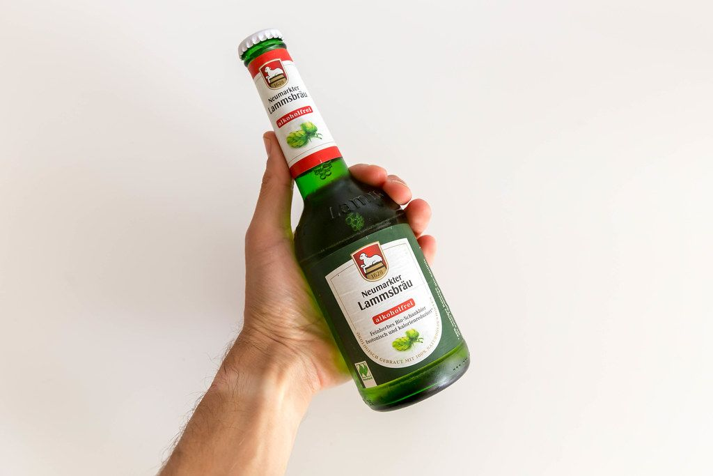 Hand holding a green beer bottle with alcohol-free organic Neumarkter Lammsbräu in front of a white background