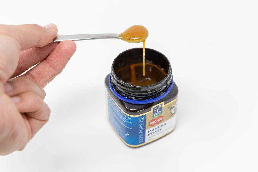 Hand holding a spoon of liquid honey over a  Manuka honey jar
