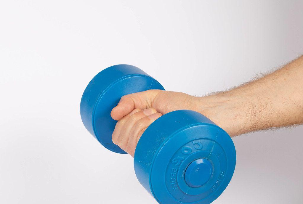 Hand holding blue dumbbell on white background (Flip 2019)