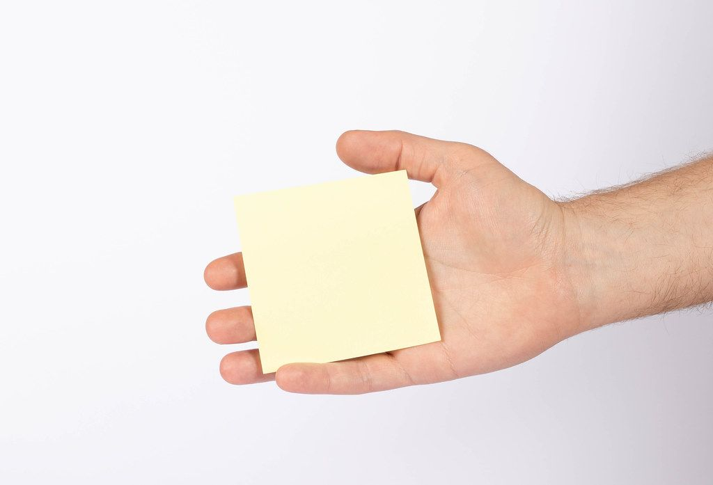 Hand holding empty yellow paper isolated on white background (Flip 2019)
