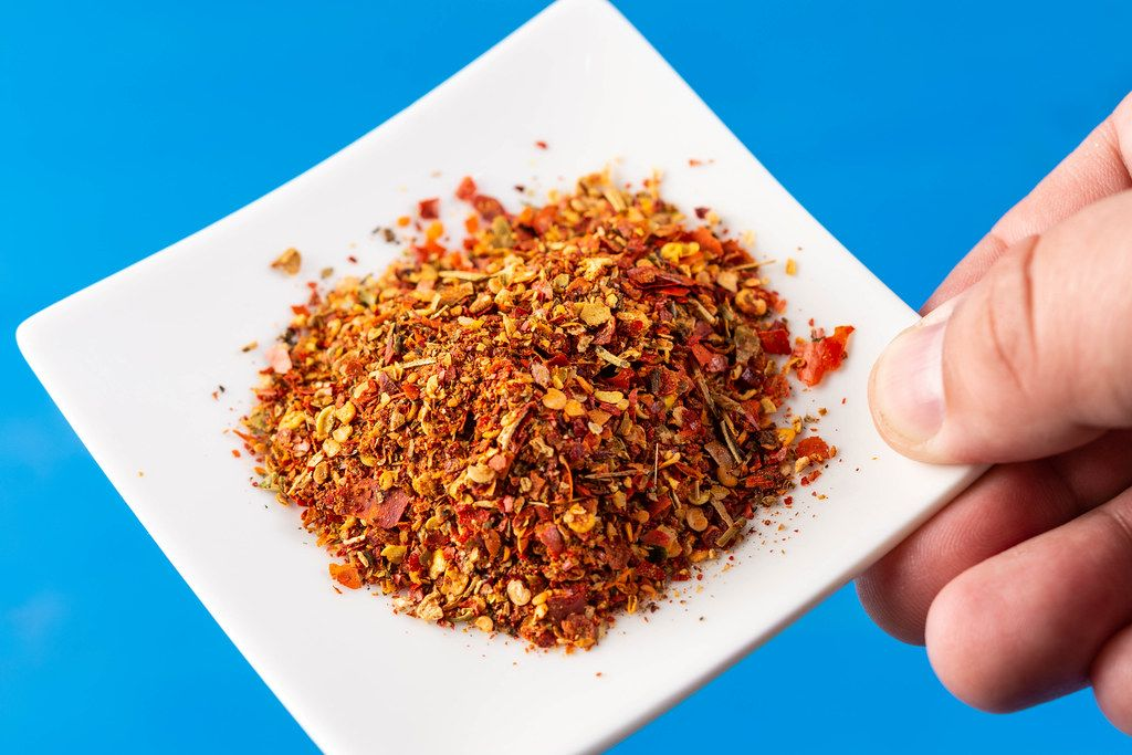 Hand holding plate with Red Grated Chilly Pepper (Flip 2019)