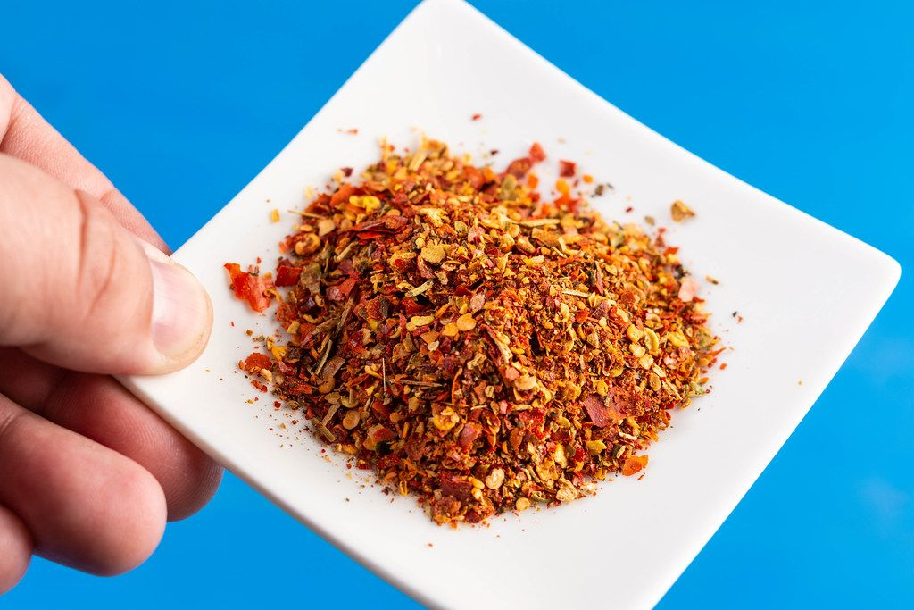 Hand holding plate with Red Grated Chilly Pepper