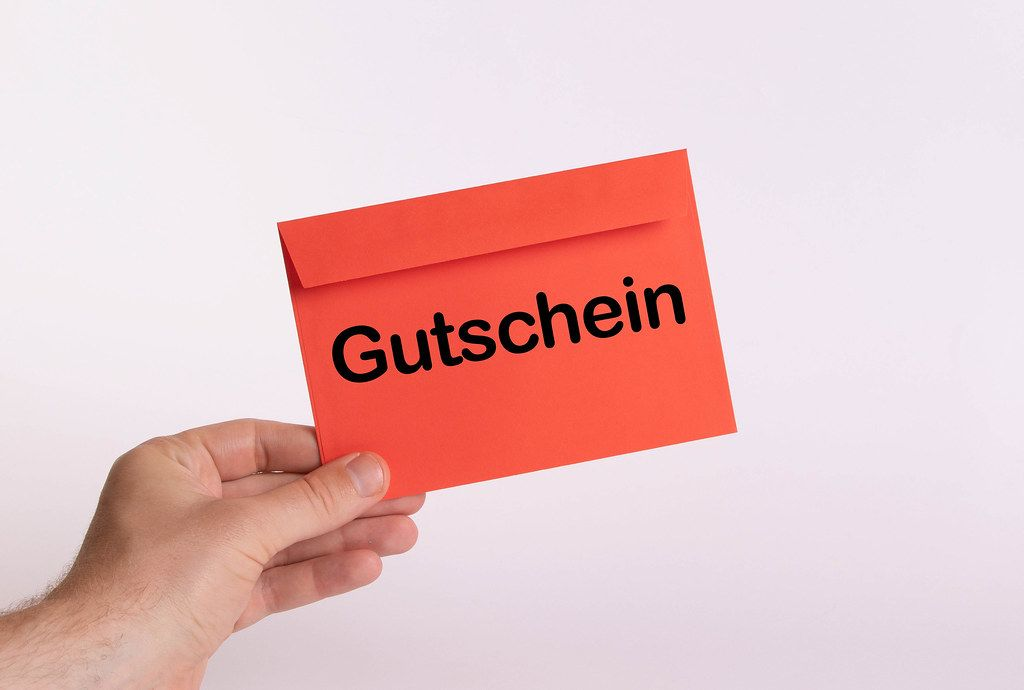 Hand holding red envelope with Gutschein text