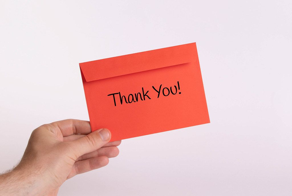 Hand holding red envelope with Thank You! text