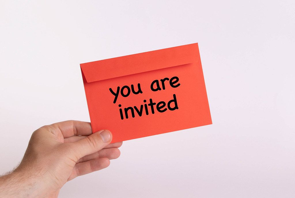 Hand holding red envelope with you are invited text