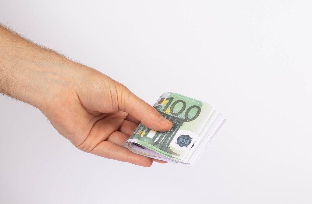 Hand holding stack of Euro bills