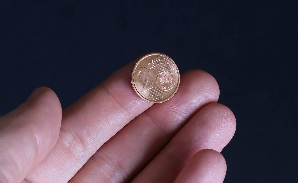 Hand holding two Euro cent coin