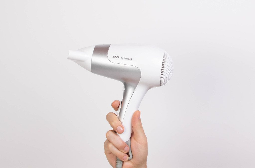 Hand holding white blow dryer