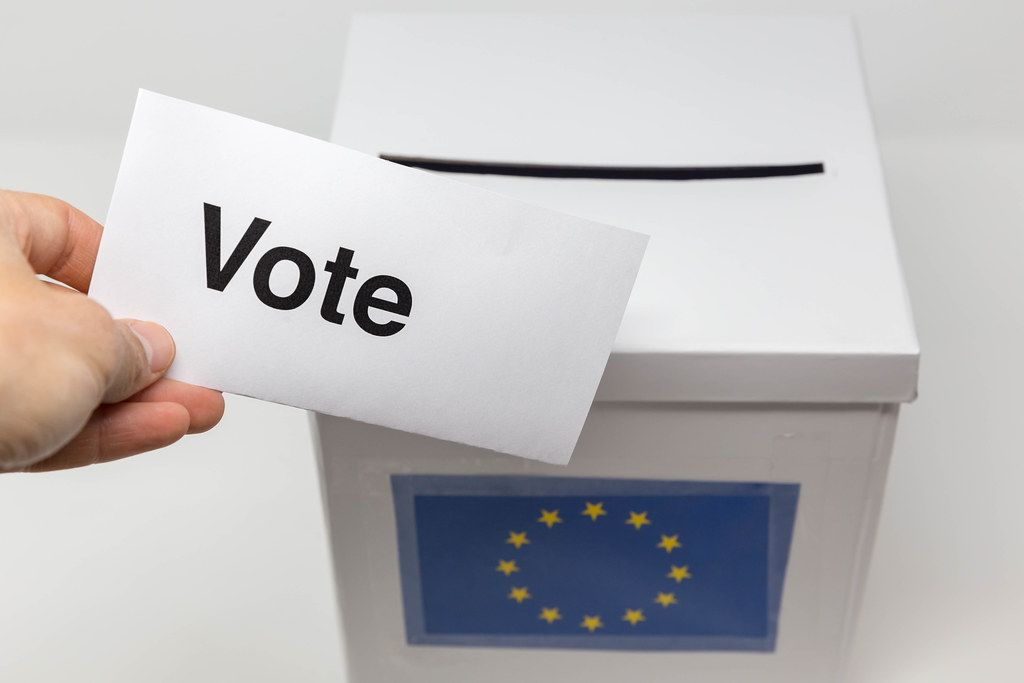 Hand holds a ballot paper with the text