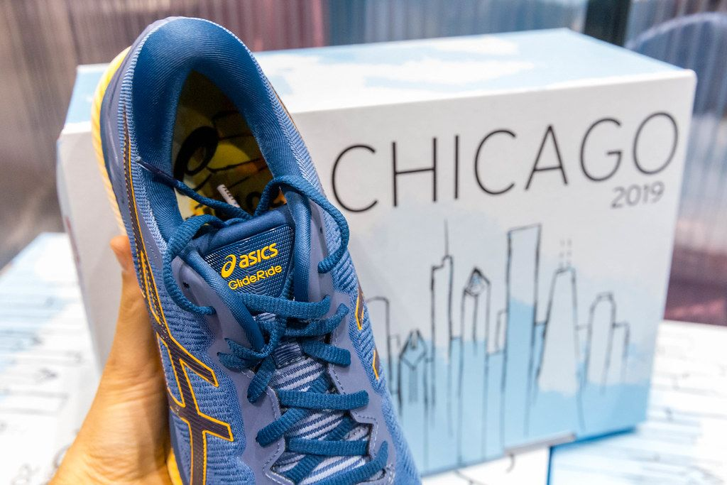 Hand holds blue asics GlideRide running shoes with Chicago marathon 2019 design printed on a shoe box