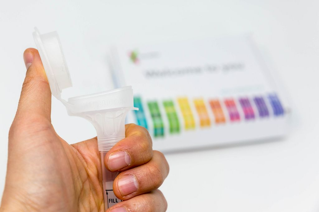 Hand holds Saliva Collection Kit Tube from 23andMe with open funnel lid to test health and ancestry with personal genetic in front of blurry background