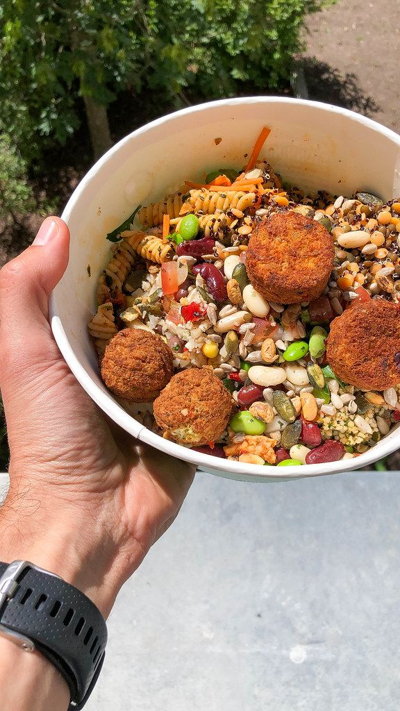 Hand holds self mixed food by PicaDeli salad bar: Powerkorn mix with pasta & vegetarian tomato-basil vegetable balls, in a to-go bowl