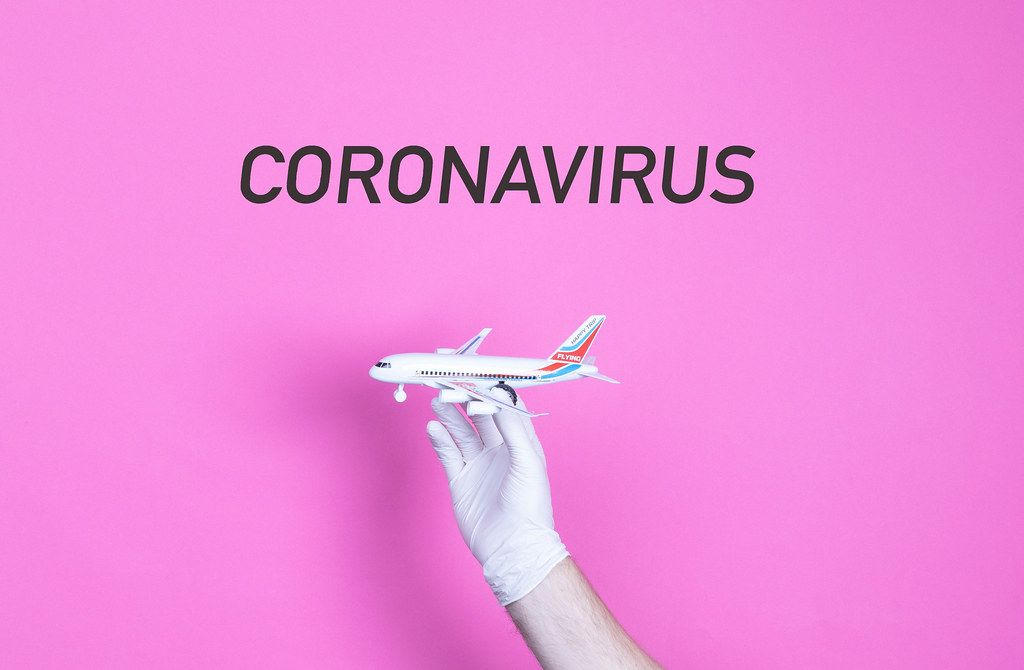 Hand in medical glove holding small airplane with Coronavirus text
