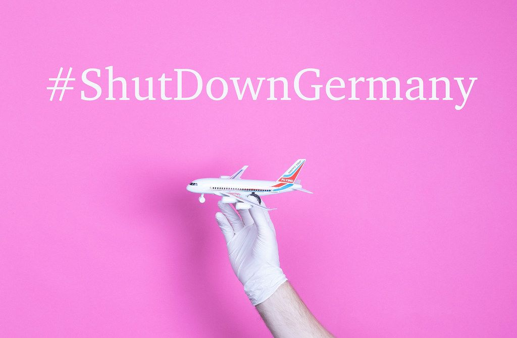 Hand in medical glove holding small airplane with #ShutDownGermany text