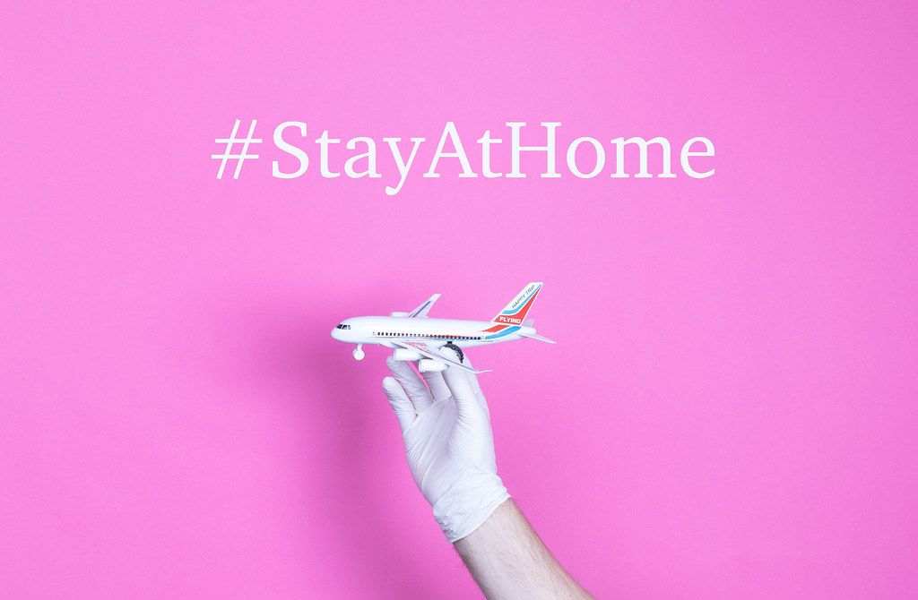 Hand in medical glove holding small airplane with #StayAtHome text.jpg