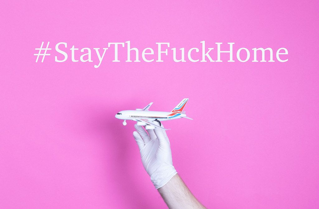 Hand in medical glove holding small airplane with #StayTheFuckHome text.jpg