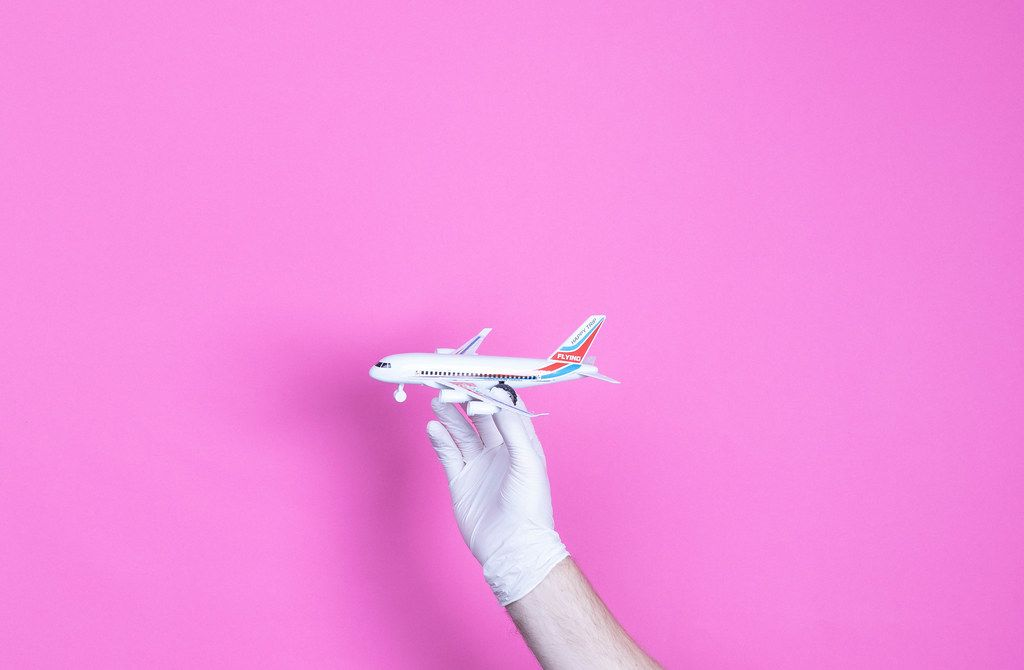 Hand in medical glove holding small airplane