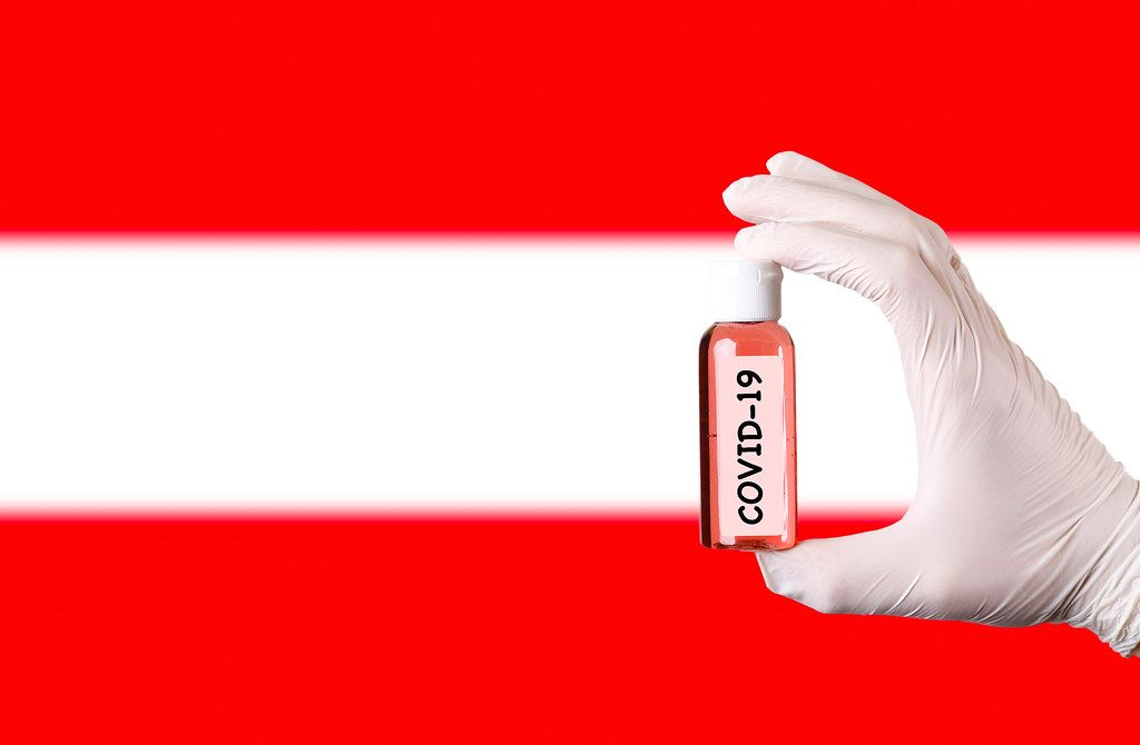 Hand in protective gloves holding COVID-19 test tube in front of flag of Austria
