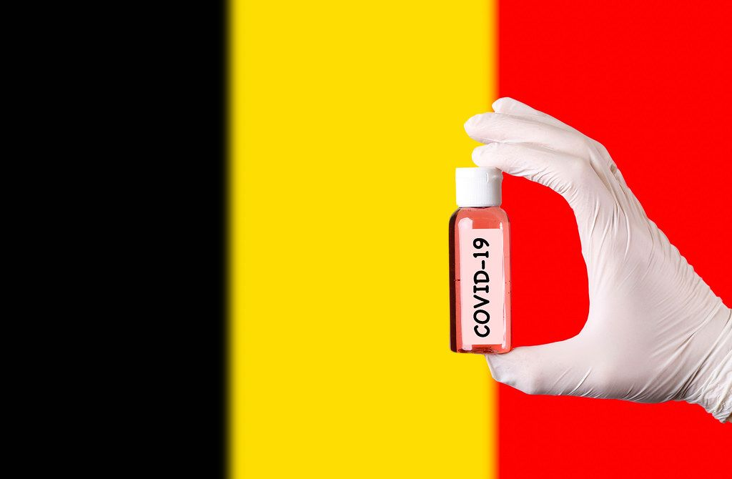 Hand in protective gloves holding COVID-19 test tube in front of flag of Belgium