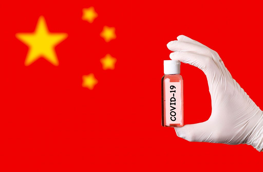 Hand in protective gloves holding COVID-19 test tube in front of flag of China