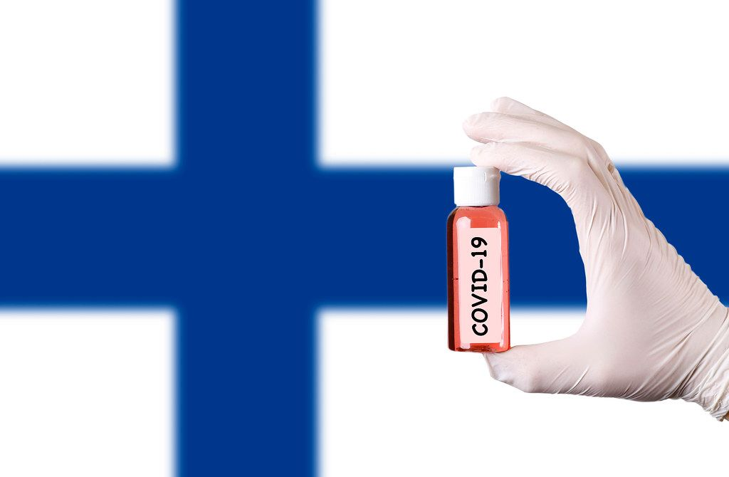 Hand in protective gloves holding COVID-19 test tube in front of flag of Finland