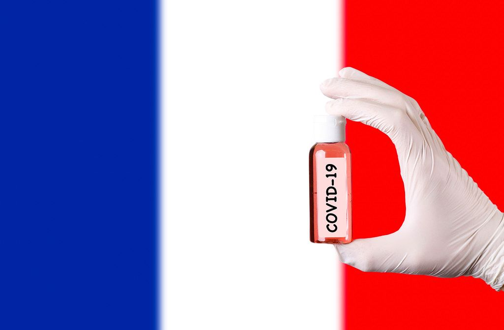 Hand in protective gloves holding COVID-19 test tube in front of flag of France