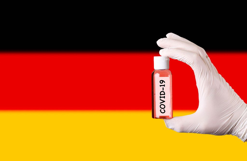 Hand in protective gloves holding COVID-19 test tube in front of flag of Germany
