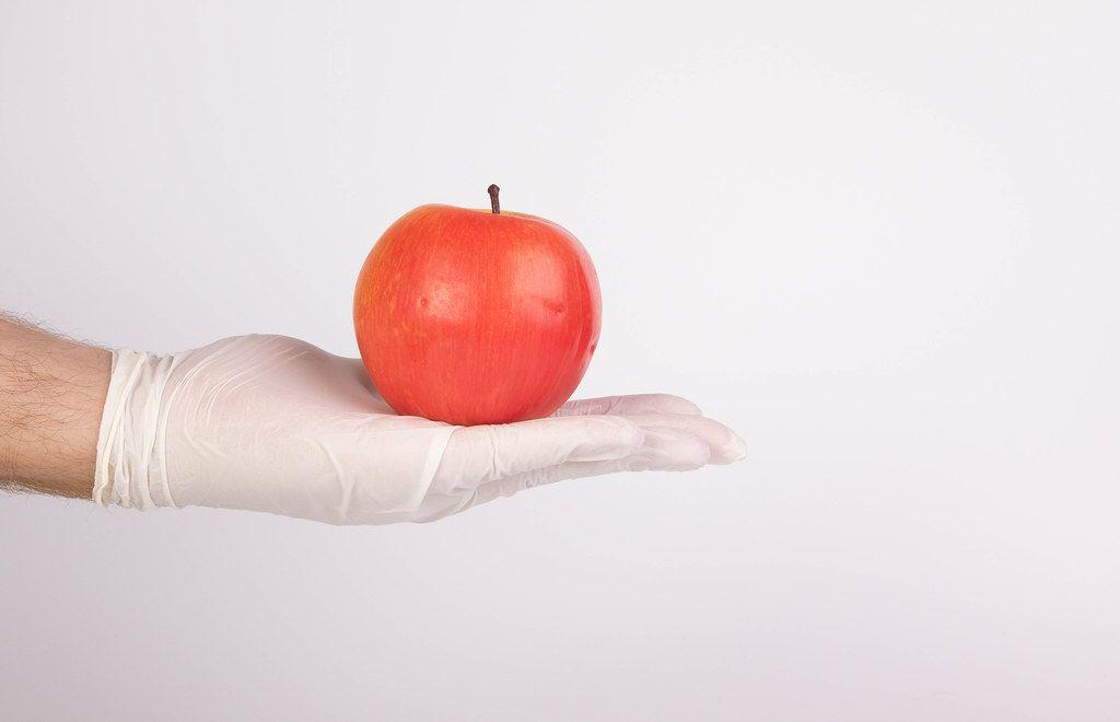 Hand mit Latexhandschuh / Einmalhandschuh hält einen roten Apfel vor weißem Hintergrund