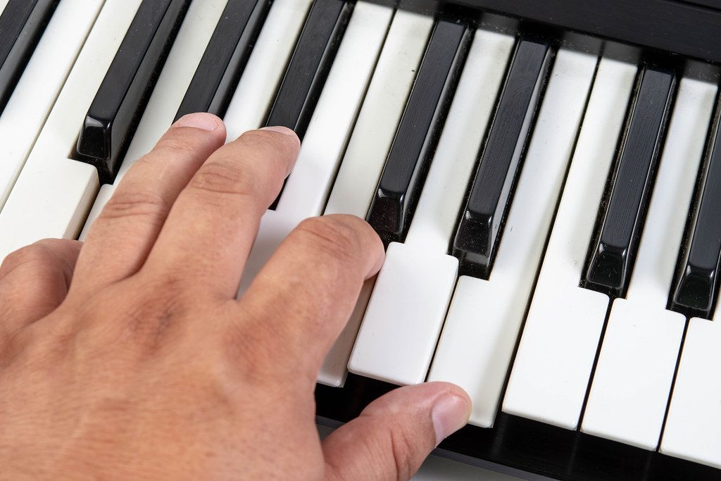 Hand on black and white synth keyboard playing