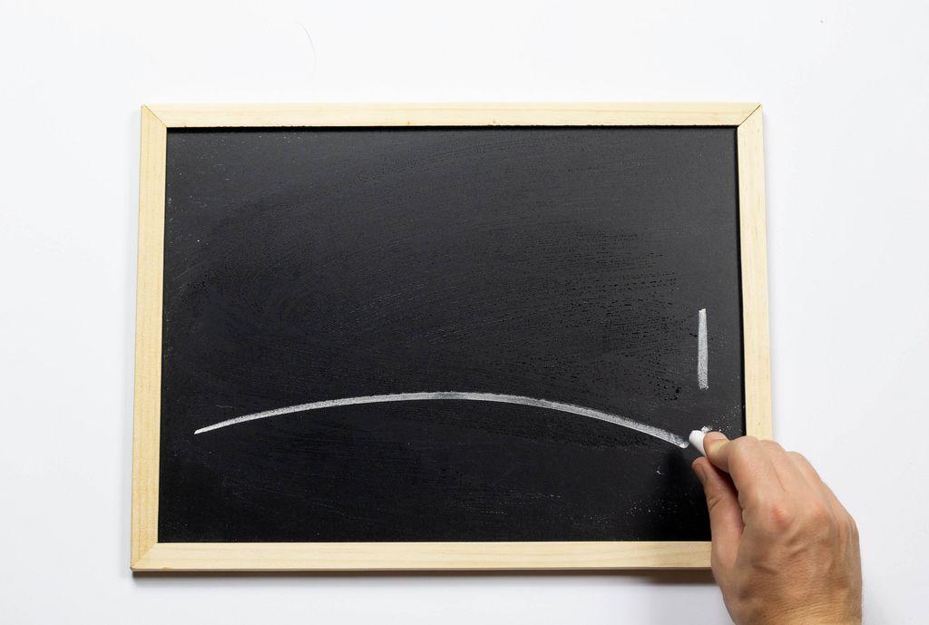 Hand schriebt mit Kreide auf einer Tafel