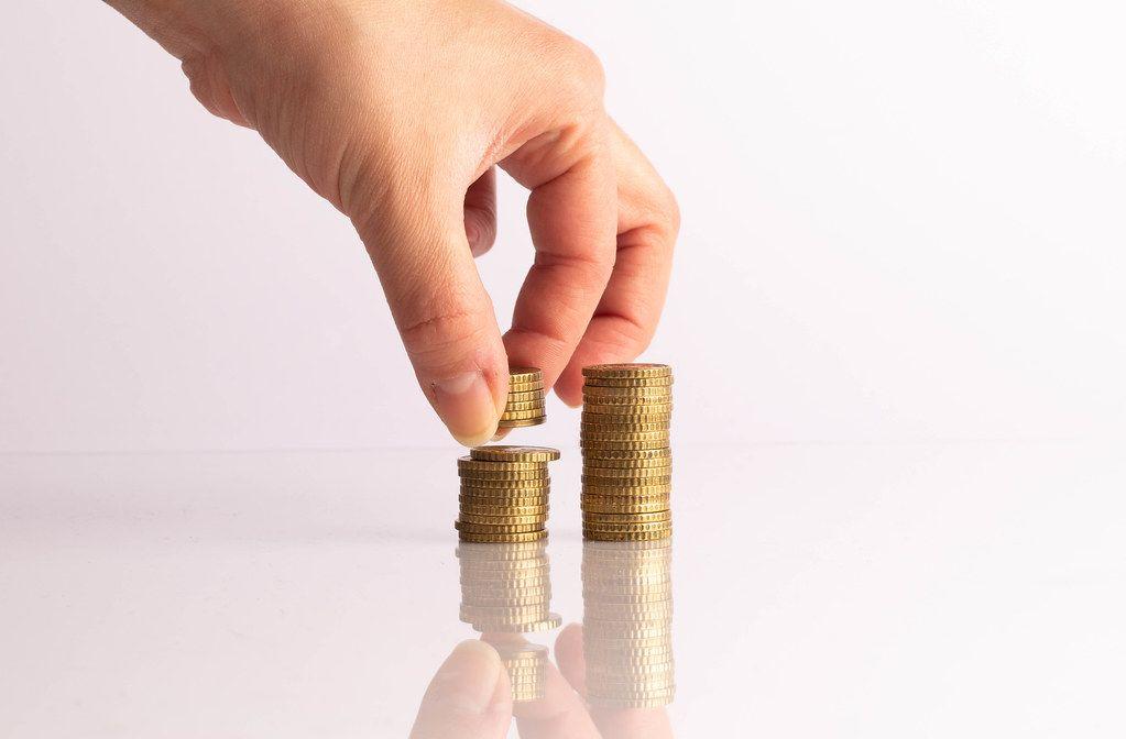 Hand setzt Münzen auf einen Stapel